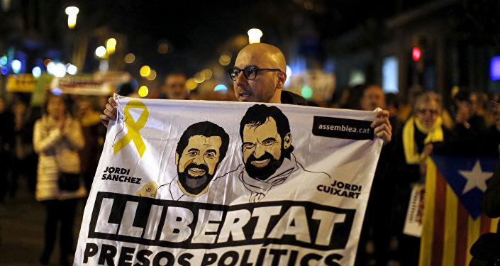 Em Barcelona, na Espanha, um manifestante segura um cartaz com o rosto de Jordi Sanchez, da Assembleia Nacional da Catalunha, e Jordi Cuixart, líder da Omnium Cultural, em apoio aos políticos presos.