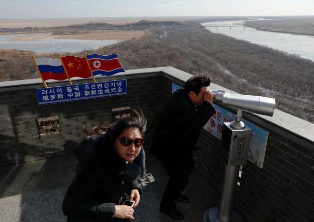 Turista usa binóculo para olhar à Coreia do Norte de uma torre construída na parte chinesa da tripla fronteira entre a Rússia, a China e a Coreia do Norte