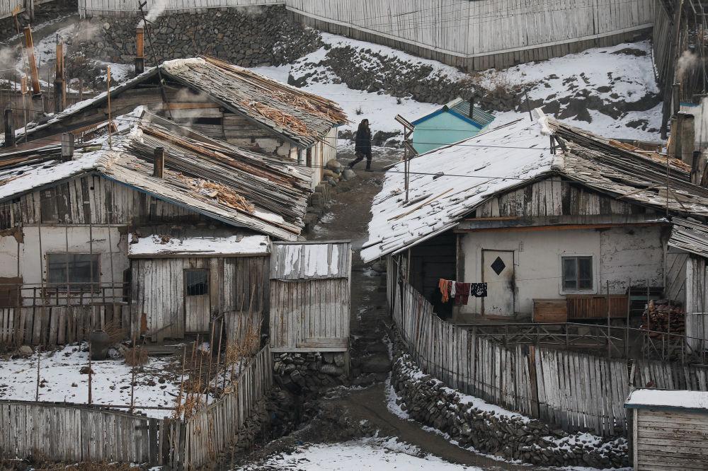 Mulher norte-coreana, captada a partir da parte chinesa da fronteira, caminha entre as moradias da cidade de Hyesan