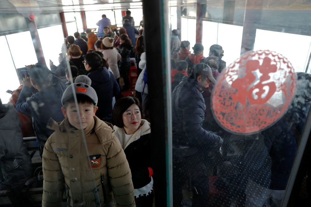 Turistas passeiam em uma lancha que parte do lado chinês da fronteira