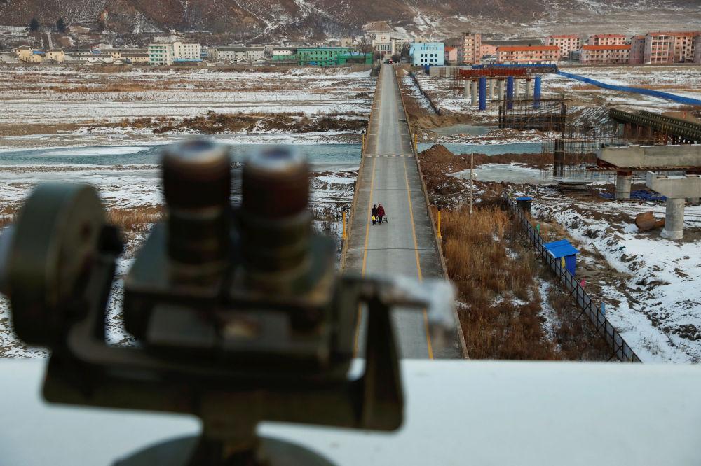 Mulher fotografada da parte chinesa da fronteira é vista do ponto de observação usado pelos turistas para dar uma olhada à Coreia do Norte