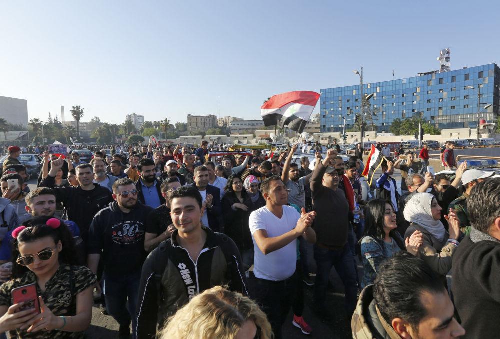 Participantes de uma manifestação contra os ataques aéreos da coalizão internacional na praça Umayyad, em Damasco