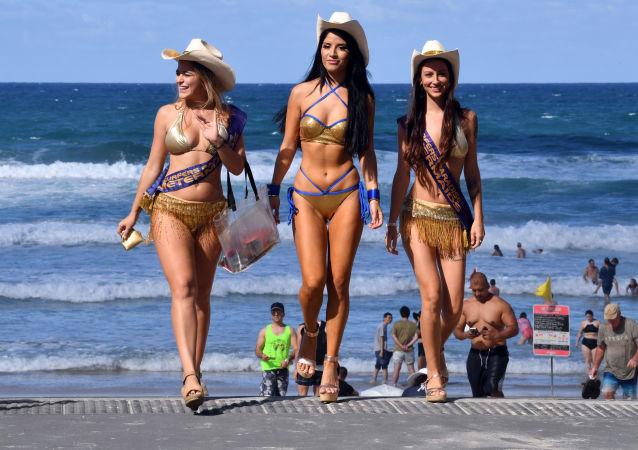 Meninas controladoras de estacionamentos pagos vigiam a praia Surfers Paradise, na cidade australiana de Gold Cost