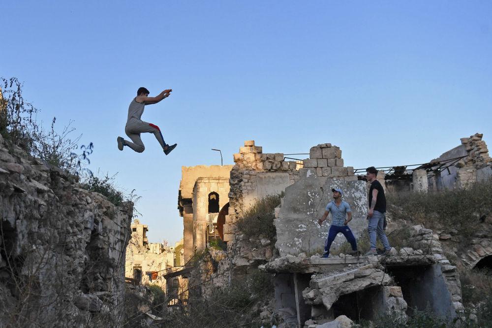 Jovens sírios praticam parkour na cidade síria de Aleppo