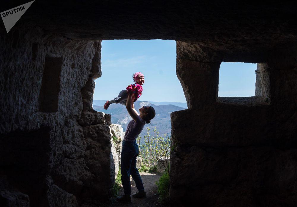 Mulher com criança no território da cidade em cavernas de Mangup, na Crimeia