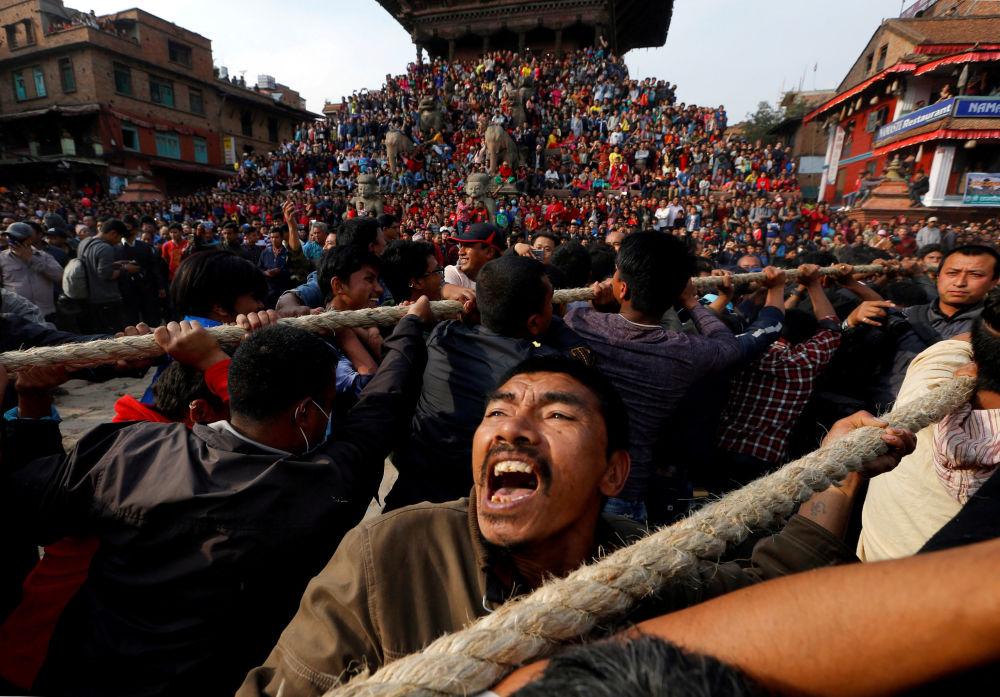 Nepaleses puxam os cabos fixados no carro do deus Bhairab durante um festival religioso