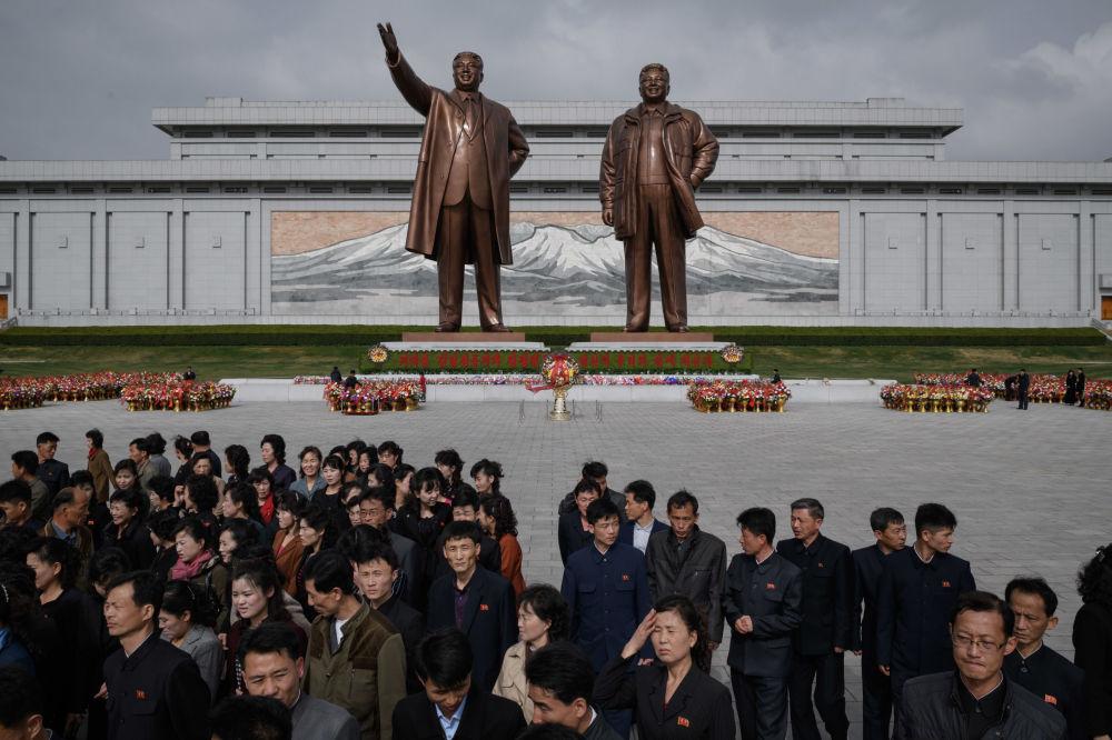Pessoas perto dos monumentos dos líderes norte-coreanos Kim Il-sung e Kim Jong-il, Pyongyang, 15 de abril de 2018