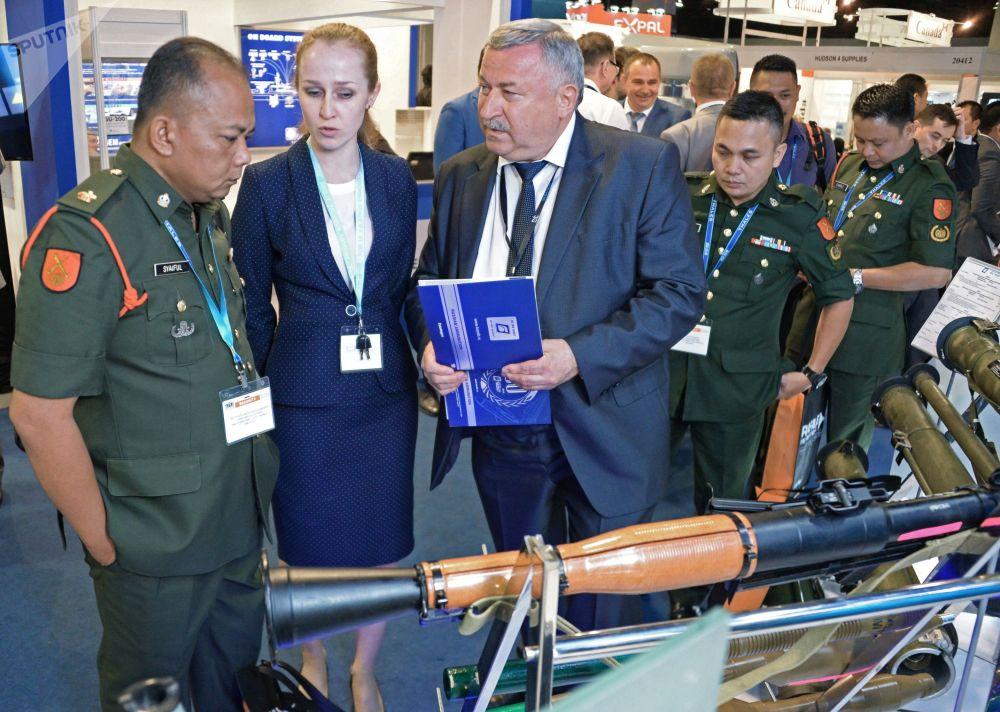 Participantes da exposição Defence Services Asia (DSA) perto do pavilhão com o lança-granadas russo RPG-7V1.