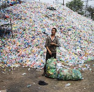 Trabalhador chinês separa latas de plástico nos arredores de Pequim