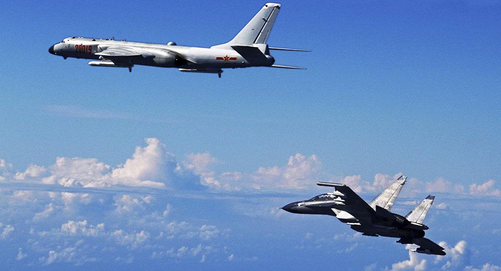 Caça Su-30 do Exército Popular de Libertação da China (à direita) voando perto do bombardeiro H-6K durante manobras no mar da China Oriental