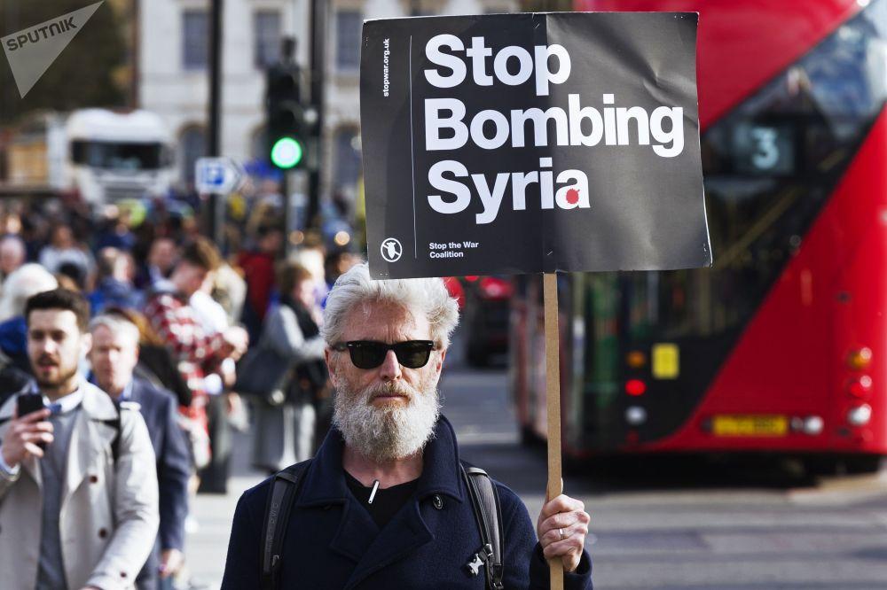 Homem segurando cartaz apelando para não bombardear a Síria durante um protesto contra os ataques à Síria em Londres.