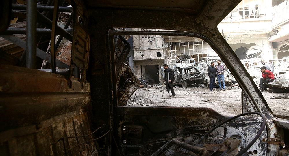 Um homem de muletas caminha em um local danificado na cidade sitiada de Douma, em Ghouta Oriental, em Damasco, na Síria.
