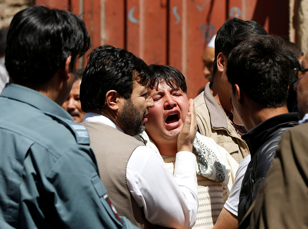 Um homem choram enquanto outros tentam confortá-lo no local de um ataque suicida em Cabul.