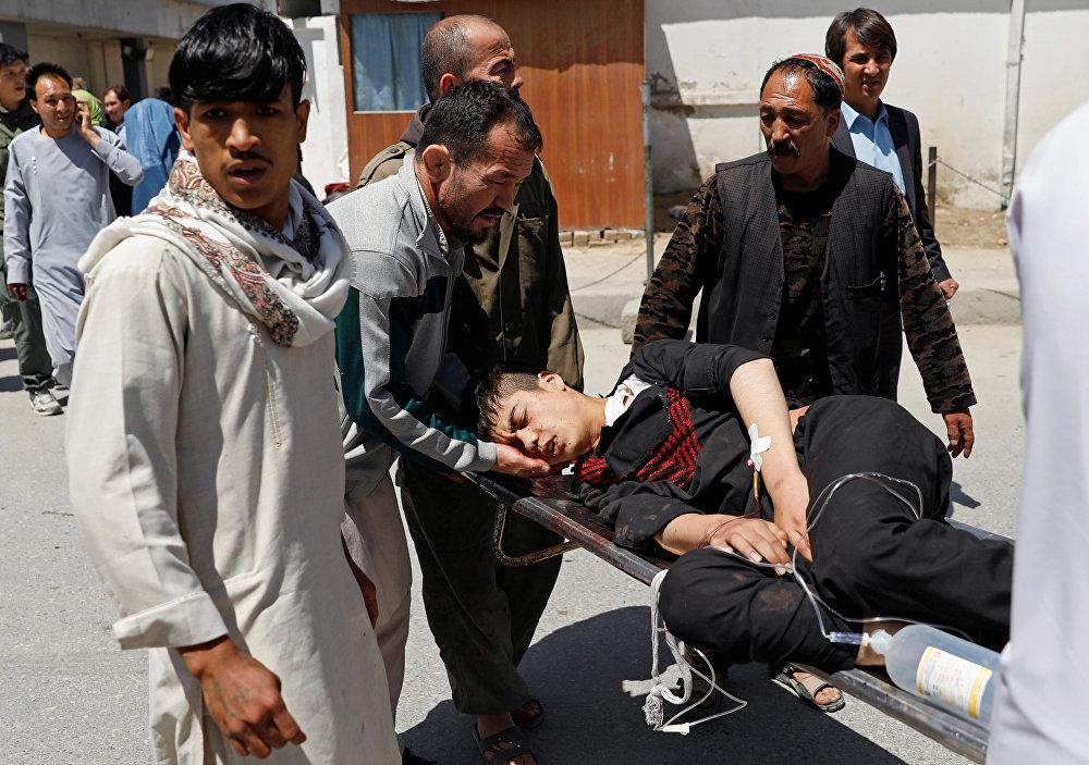 Parentes carregam um homem ferido do lado de fora de um hospital após um ataque suicida em Cabul.