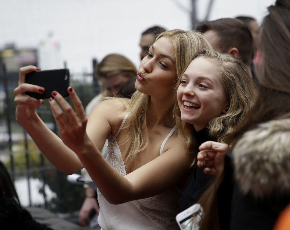 Jovens fãs tiram selfies com sua favorita modelo estadunidense Gigi Hadid em Nova York