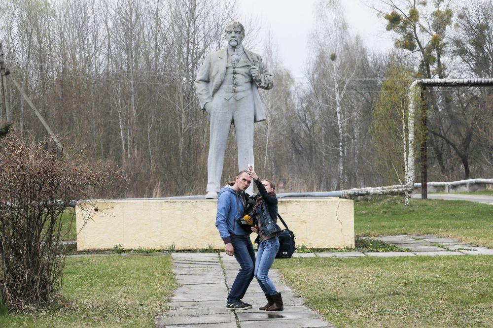 Jornalistas tirando selfies perto do monumento de Vladimir Lenin (líder fundador da União das Repúblicas Socialistas Soviéticas) em Chernobyl