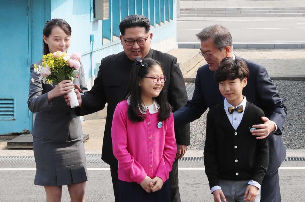 Presidente sul-coreano Moon Jae-in e seu homólogo norte-coreano, acompanhado por pessoas de confiança, posam com buquê de flores durante encontro na localidade de Panmunjom