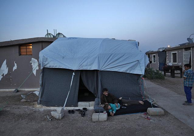 Homem deslocado de Ghouta Oriental, Síria, com sua família
