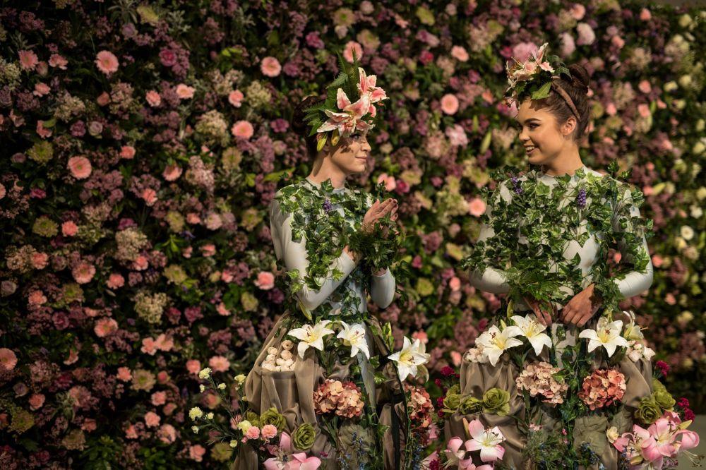 Dançarinas Alison Parsons e Georgia Paton-Durrant posam frente a uma exposição de flores durante um festival em Harrogate, na Inglaterra
