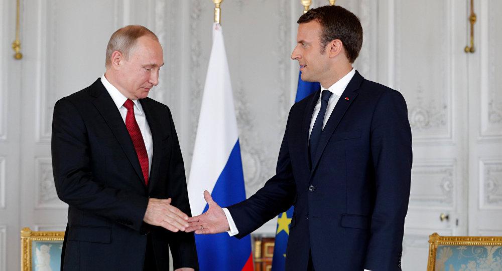 Presidente francês, Emmanuel Macron, apertando a mão ao homólogo russo, Vladimir Putin, no Palácio de Versalhes (foto de arquivo)