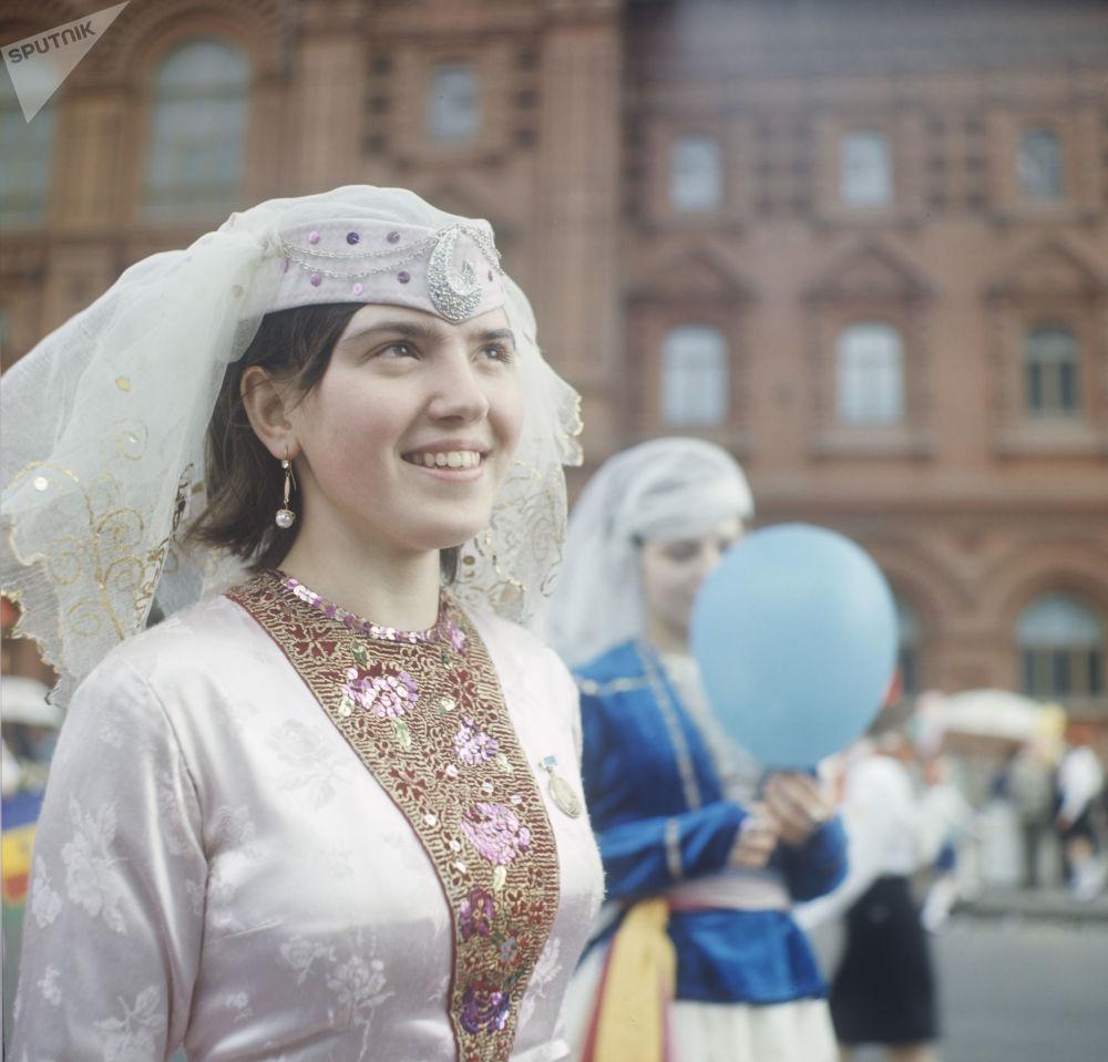 Participante do desfile festivo de 1º de maio; estudante de Moscou vestida com traje nacional georgiano, em 1969