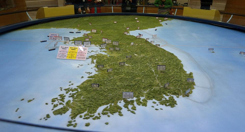 Visitantes olhando para o mapa da península coreana no observatório da reunificação em Paju, Coreia do Sul