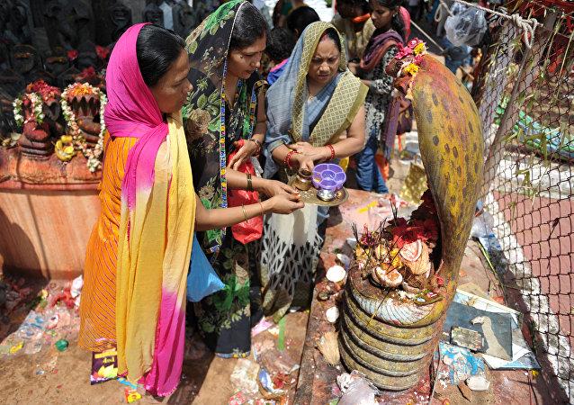 Mulheres hindus oferecem orações a estátuas de cobras durante o festival de Nag Panchami, Índia, 28 de julho de 2017