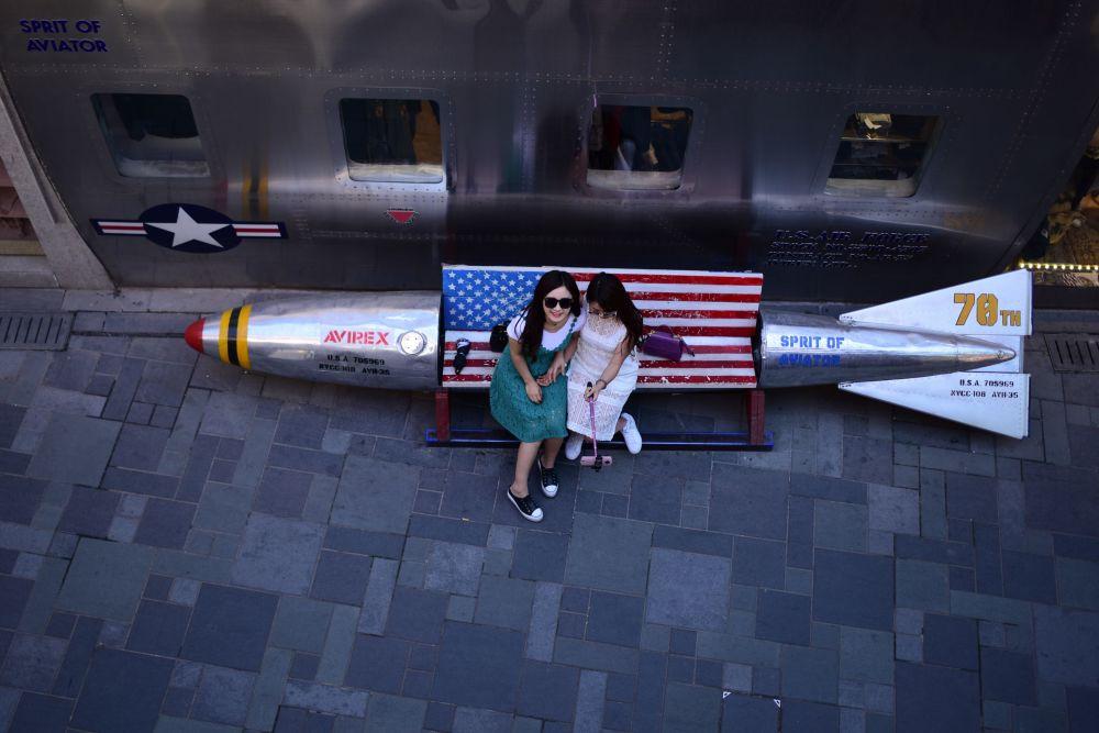Moças tiram fotos em um banco em forma de míssil, em Pequim