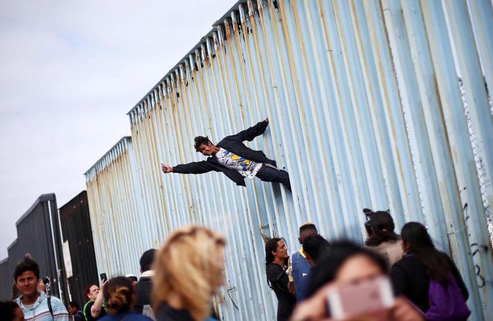 Participante de uma manifestação de imigrantes da América Central sobe ao muro que divide o México e os EUA