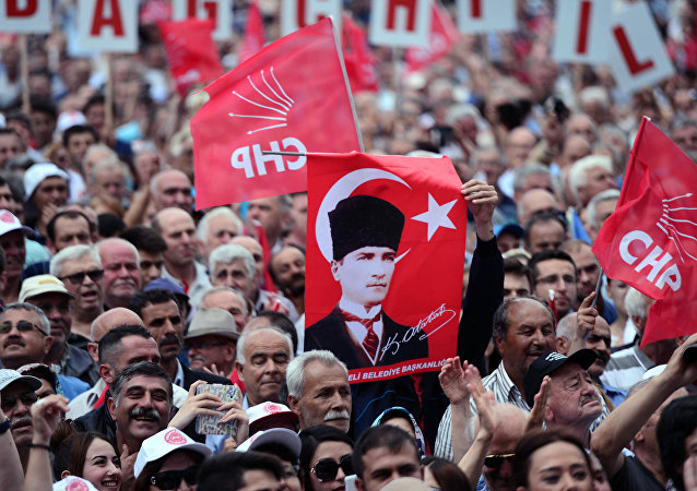 People hold a poster of Mustafa Kemal Ataturk, the founder of modern Turkey, as they listen to Turkey's main opposition Republican People's Party, CHP, leader Kemal Kilicdaroglu in Luleburgaz, Turkey, Wednesday, May 27, 2015