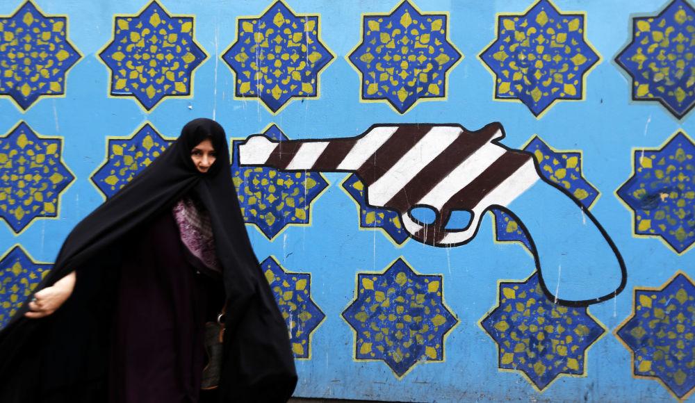 Cidadã iraniana junto a grafite perto da ex-embaixada dos EUA em Teerã