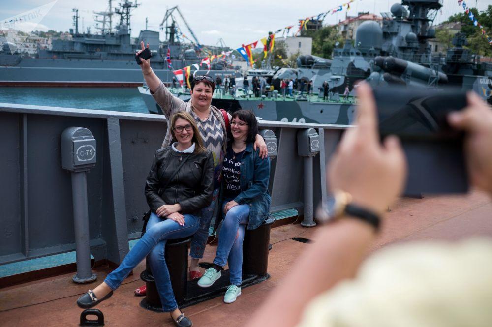 Visitantes se fotografando durante a exibição dos navios militares