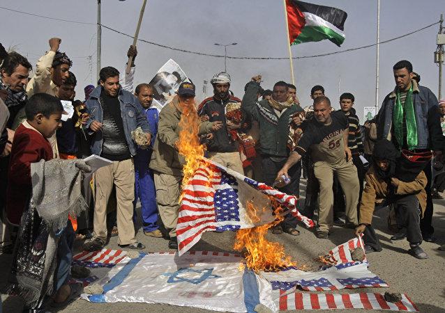 Manifestantes iraquianos queimando as bandeiras dos EUA e de Israel como gesto de apoio à Palestina