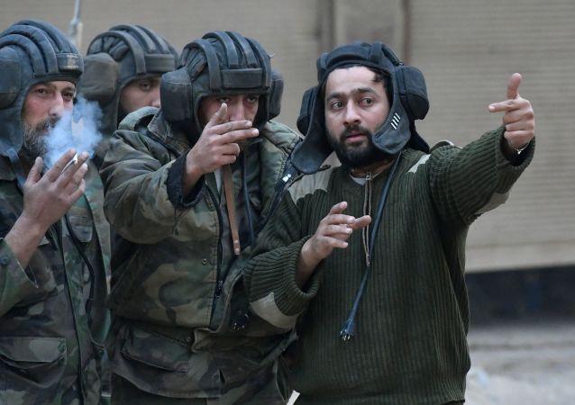 Militares na área do antigo campo de refugiados palestinos Yarmouk no subúrbio a sul de Damasco
