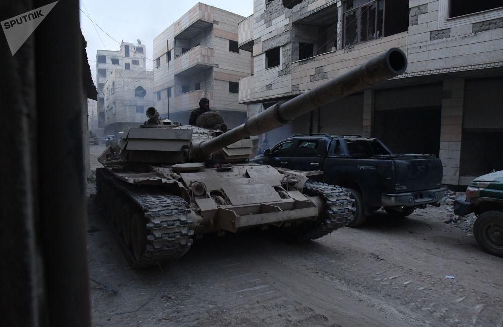 Tanque das Forças Armadas sírias na área do antigo campo de refugiados palestinos em Yarmouk, no subúrbio a sul de Damasco