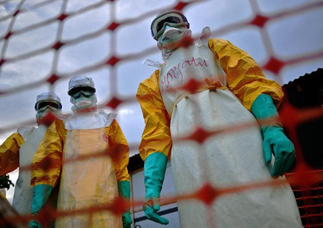 Uma foto de arquivo tirada em 14 de agosto de 2014 mostra a equipe médica de Médicos Sem Fronteiras (MSF) vestindo roupas de proteção tratando o corpo de uma vítima de Ebola em suas instalações em Kailahun.
