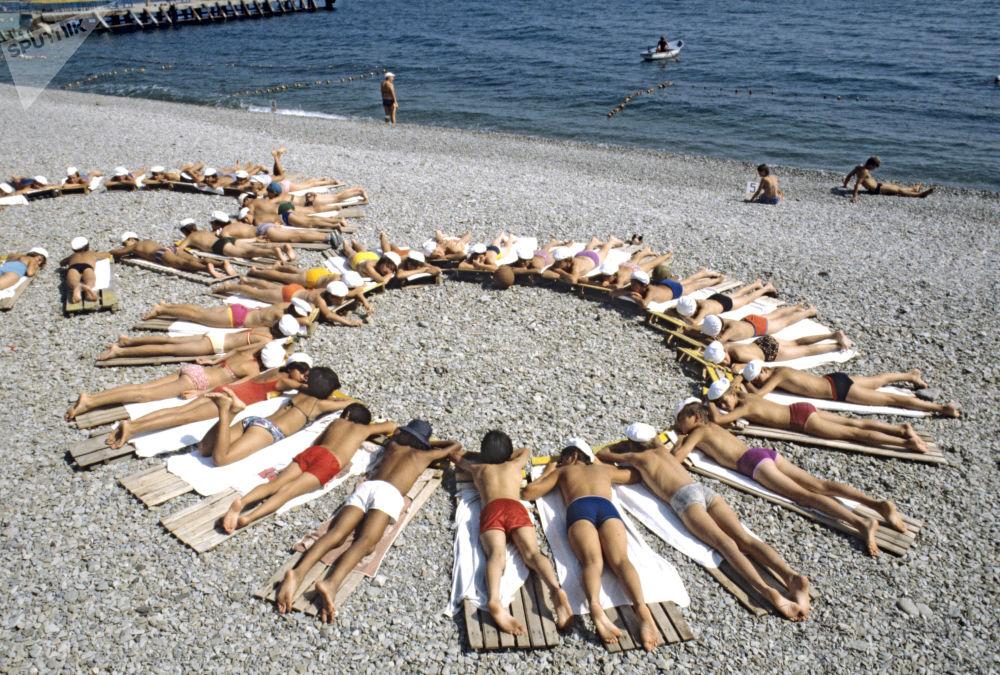 Pioneiros tomam banhos de sol junto ao mar Negro, no campo de Artek, na Crimeia, em 1984