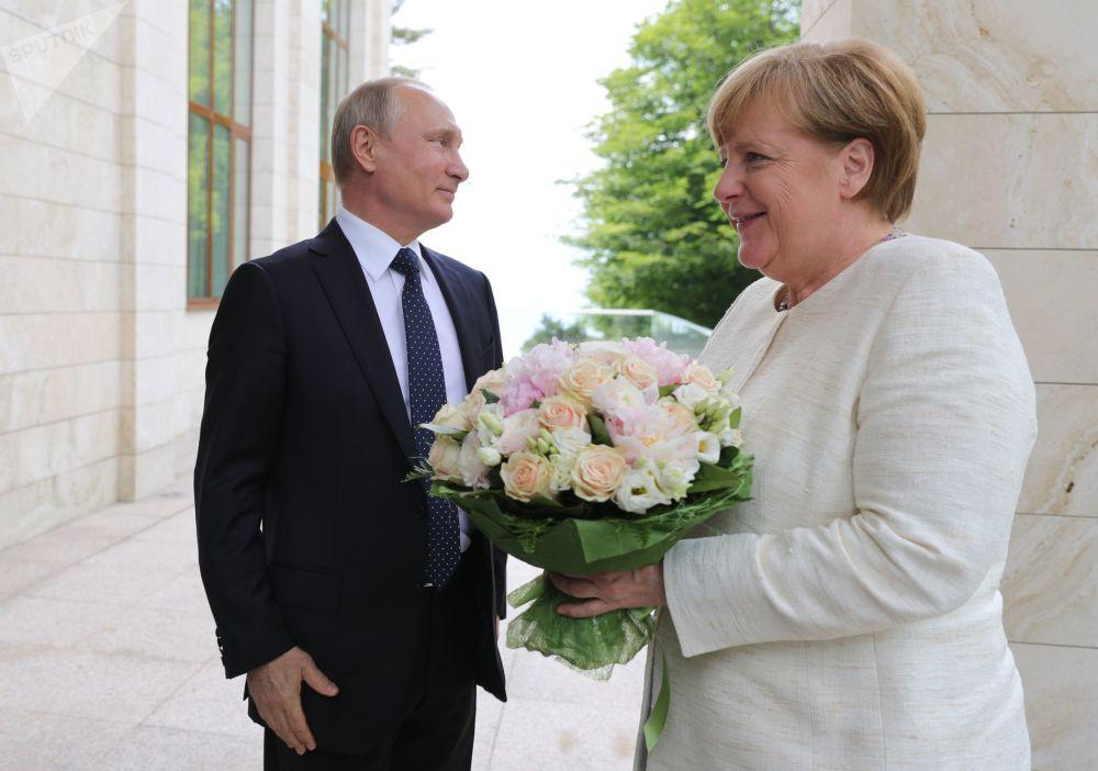 O presidente da Rússia, Vladimir Putin, oferece um buquê de flores à chanceler da Alemanha, Angela Merkel, antes da reunião dos dois líderes em Sochi, na Rússia