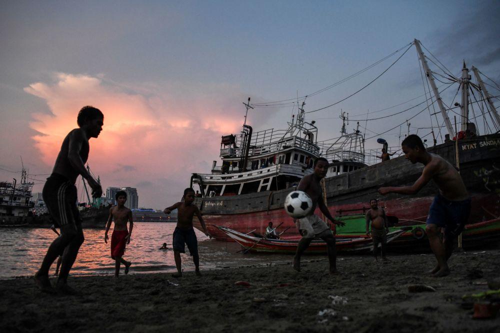 Crianças jogam futebol na margem do rio Yangon, Mianmar