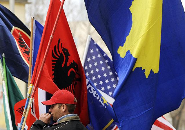 Um homem albanês do Kosovo segura bandeiras em Pristina em 16 de fevereiro de 2011 em preparação para o terceiro aniversário da declaração de independência do Kosovo