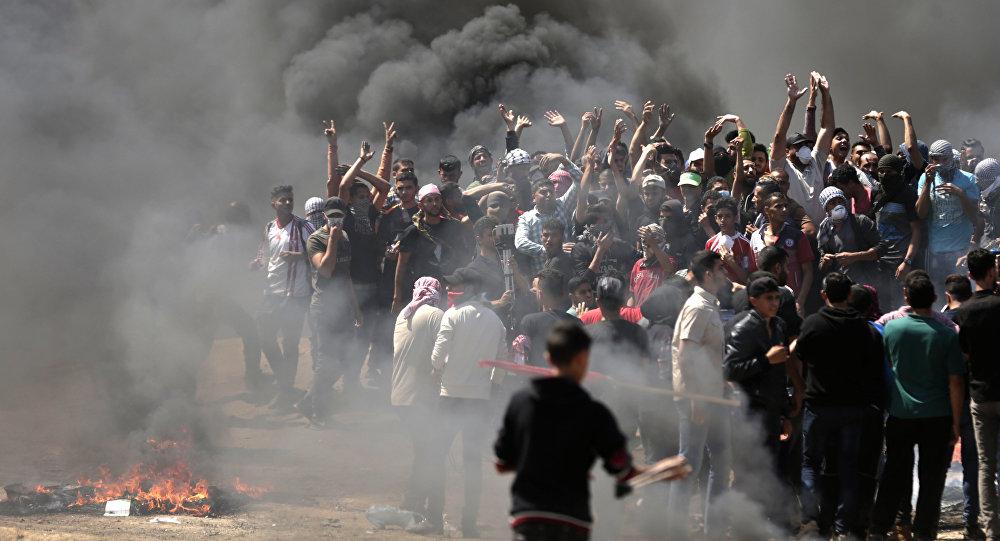 Manifestantes palestinos queimam pneus perto da fronteira entre Gaza e Israel, a leste da cidade de Gaza, enquanto palestinos se preparam para protestos pela posse da embaixada dos Estados Unidos, após a controversa mudança para Jerusalém, em 14 de maio de 2018