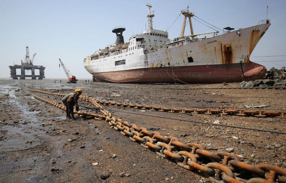 Operários puxam uma corrente ligada a torre de extração de petróleo desmantelada, na Índia