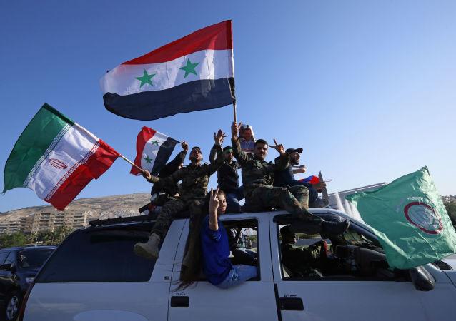 Partidários do governo sírio acenam com bandeiras sírias, iranianas e russas enquanto cantam palavras de ordem contra o presidente norte-americano Trump durante manifestações em Damasco.