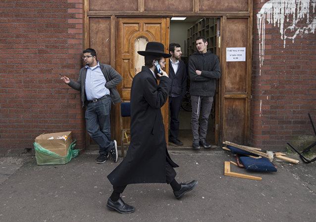 Um judeu ortodoxo fala em seu celular enquanto passa pela sinagoga Ahavas Torá na área de Stamford Hill, ao norte de Londres (foto de arquivo).