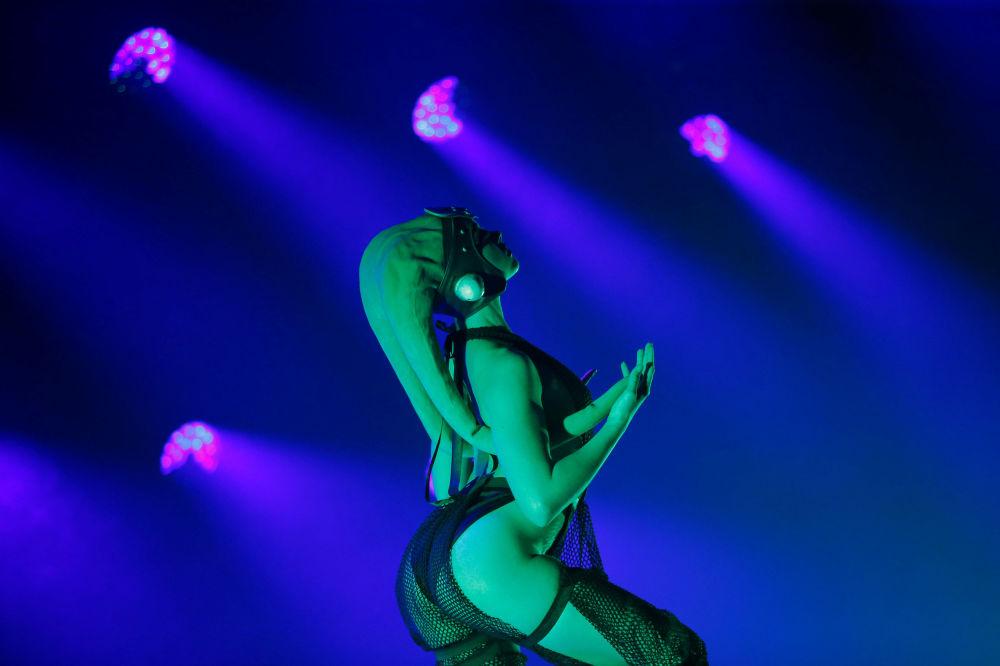 Dançarina em traje especial se apresenta no palco em Los Angeles iluminada por luzes suaves