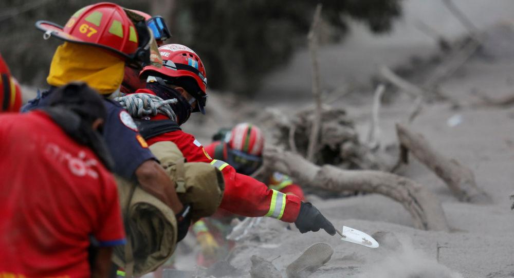 Equipes de resgate cavam a procura de corpos após a erupção do vulcão Fogo na Guatemala, em 4 de junho de 2018