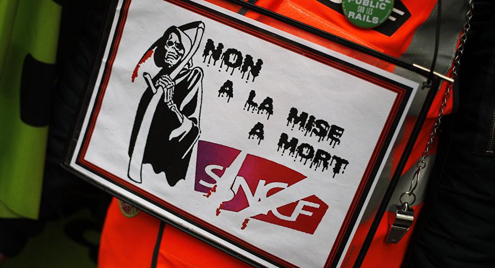 Em Paris, ferroviário protesta com pôster escrito Não à morte da SNCF. A SNCF é a operadora estatal das ferrovias francesas. O protesto faz parte de uma greve dos ferroviários contra a reforma proposta pelo governo sobre o setor.