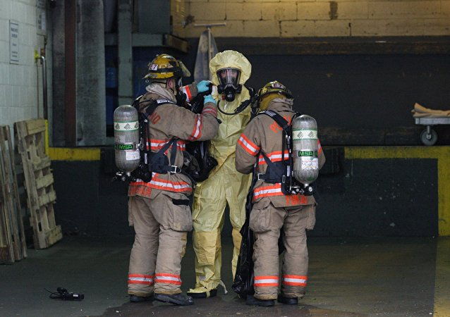Bombeiros estadunidenses ajudam seu colega que tinha coletado amostras de um objeto que supostamente continha esporos de antraz. Foto de 2012.