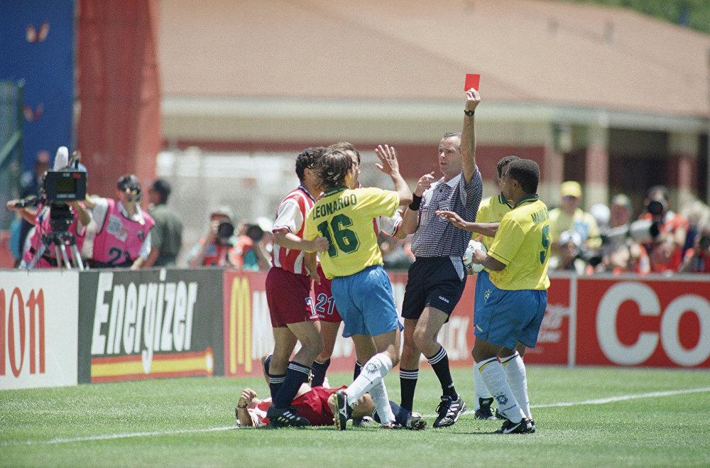 O árbitro francês Joel Quiniou dá o cartão vermelho ao zagueiro Leonardo após uma cotovelada no meio-campista Tab Ramos durante a primeira metade da partida da segunda rodada da Copa em Stanford, Califórnia, 4 de julho 1994. O Brasil venceu por 1 a 0 e enfrentou a Holanda nas quartas de final.
