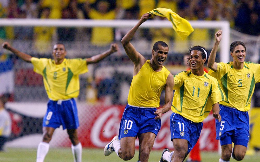 O meia brasileiro Rivaldo comemora com o zagueiro brasileiro Edmilson, o meio-campista Ronaldinho Gaúcho e Gilberto Silva após marcar um gol  durante partida do Brasil contra Bélgica na Copa do Mundo de 2002 no Japão.